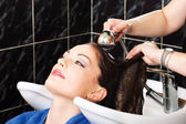 Hairdresser rinse customers hair — Stock Photo