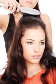 Hairdresser combing costumer's long black hair — Stock Photo