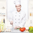 Young chef cutting onions in kitchen — Stock Photo #9990706