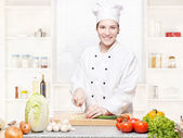 Female chef cutting onions on the cutting board in kitchen — Stock Photo