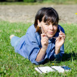 Woman lying down on the grass and puting on her eyeglasses - Stockfoto