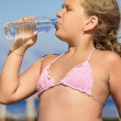 Girl dinking water on the beach — Stock Photo