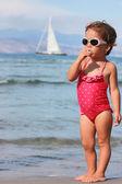 Chica con piruleta en la playa — Foto de Stock