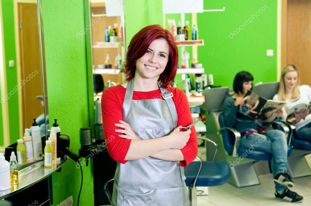 Happy hair salon owner or employee with customers in the background — Stock Photo #10082942