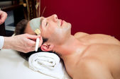 Applying a facial mask to a male customer — Stock Photo