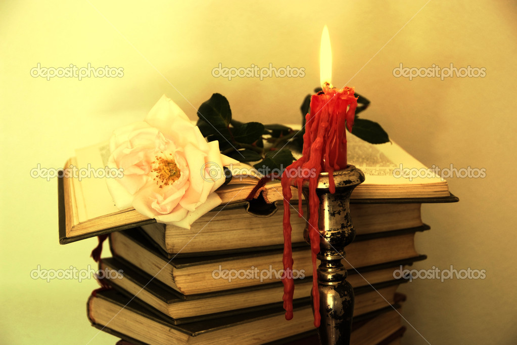 Old books, pink rose and a candle in sepia tone — Stock Photo #9450056