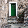 Green door in stone village - Stock Photo