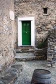 Green door in stone village — Stock Photo