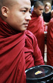 Myanmar monk carrying bowl, waiting in line for daily meal — Stock Photo