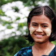 Myanmar girl with Tanaka cream on her cheeks smiling — Stock Photo