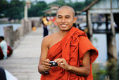 Myanmar monk taking a photo to a tourist on U-Bein bridge in Man — Stock Photo