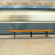 Bench on the platform with mooving fast train — Stock Photo