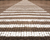 White lines of road marking on stone blocks road — Stock Photo