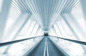 Abstract motion of escalator in symmetrical glass corridor — Stock Photo