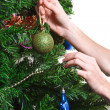 Hands with ball adorning chritmas tree isolated on white backgro — Stock Photo