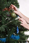 Hands with ball adorning chritmas tree isolated on white backgro — Stok fotoğraf