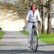 Girl walks city with bicycle — Stock Photo