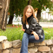 Royalty-Free Stock Photo: The girl in a black jacket sits on stones in square