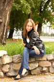 The girl in a black jacket sits on stones in square — Stok fotoğraf