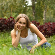 The beautiful girl in a white vest and blue jeans sits on a grass — Stock Photo #9464837
