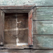Wall of the old wooden house with the hammered window — Stock Photo