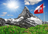Beautiful mountain Matterhorn with Swiss flag — Stock Photo