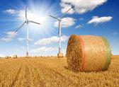 Straw bales on farmland with wind turbine — Stock Photo