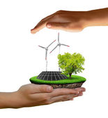 Little island with solar panel and wind turbines in the hands — Stock Photo