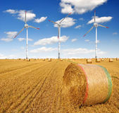 Straw bales on farmland with wind turbine — Stok fotoğraf