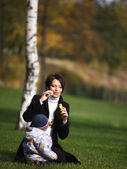 Mam and little son playing on the grace — Stock Photo