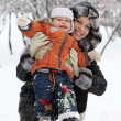 Young mam and her son in the snow - Stock Photo