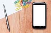 Pracoviště, mobilním telefonu, papíru, pera a klipy na pracovním stole. — Stock fotografie