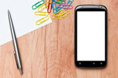 Werkplek met gsm, papier, pen en clips op werktafel. — Stockfoto