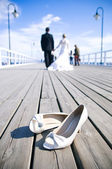 Wedding couple walking at the bridge — Photo
