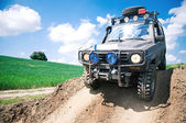Offroad through muddy field — Stockfoto