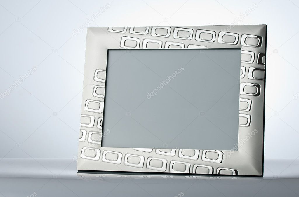 Blank silver picture frame at the table with place for your own — Stock Photo #9840789