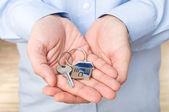 Elegant man holding key. Shallow DOF, focus on key — Stock Photo