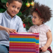 Brother and sister holding Christmas gifts — Stockfoto