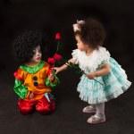 Little girl giving flowers small clown — Stock Photo
