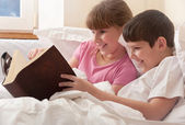 Children read book in bed — Stock Photo