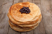 Crepes on the wooden table with cherry — Stock Photo