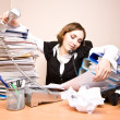 Stock Photo: Young businesswoman with tons of documents