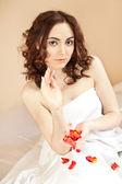Beautiful sexy woman holding a rose petals — Stock Photo