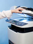 Woman's hand with working copier (focus on LCD screen) — Stock Photo