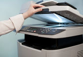 Woman's hand with working copier (focus on finger) — Stock Photo