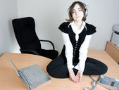 Young businesswoman sitting on the desk — Stock Photo