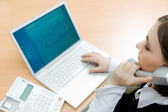 Woman working on laptop (focus on woman) — Stock Photo