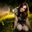 Young woman sitting on the grass - Stock Photo