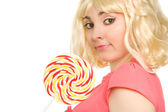 Beautiful blond woman with lollipop (focus on face) — Stock Photo