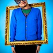 Young funny man with gold frame — Stock Photo